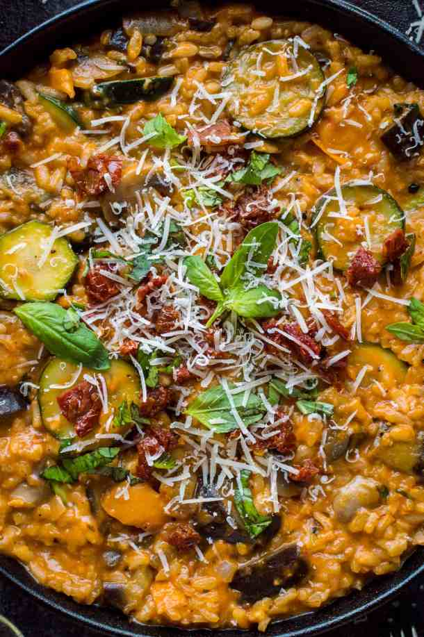 Close-up of ratatouille risotto topped with sundried tomatoes, basil and parmesan