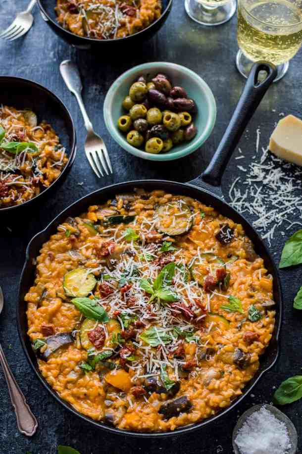 Angled shot of vegetarian ratatouille risotto served in a cast iron skillet with olives