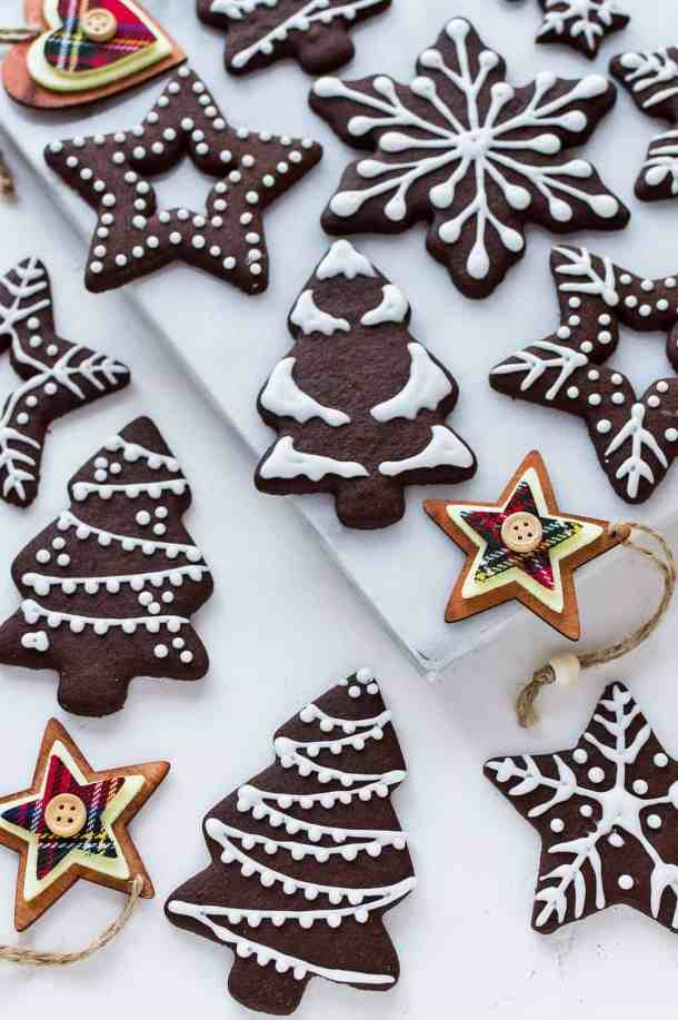 Angled photo of iced chocolate gingerbread biscuits on a white marble board with wooden Christmas tree decorations.