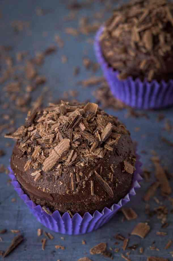 Two vegan chocolate cupcakes topped with chocolate shavings.
