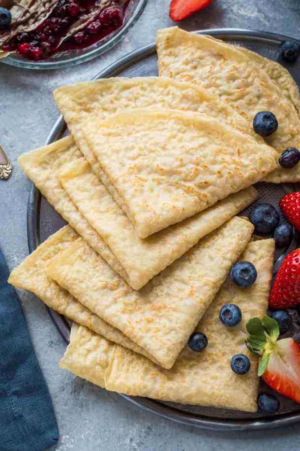 A plateful of egg and dairy free vegan crepes (pancakes) with fresh berries.