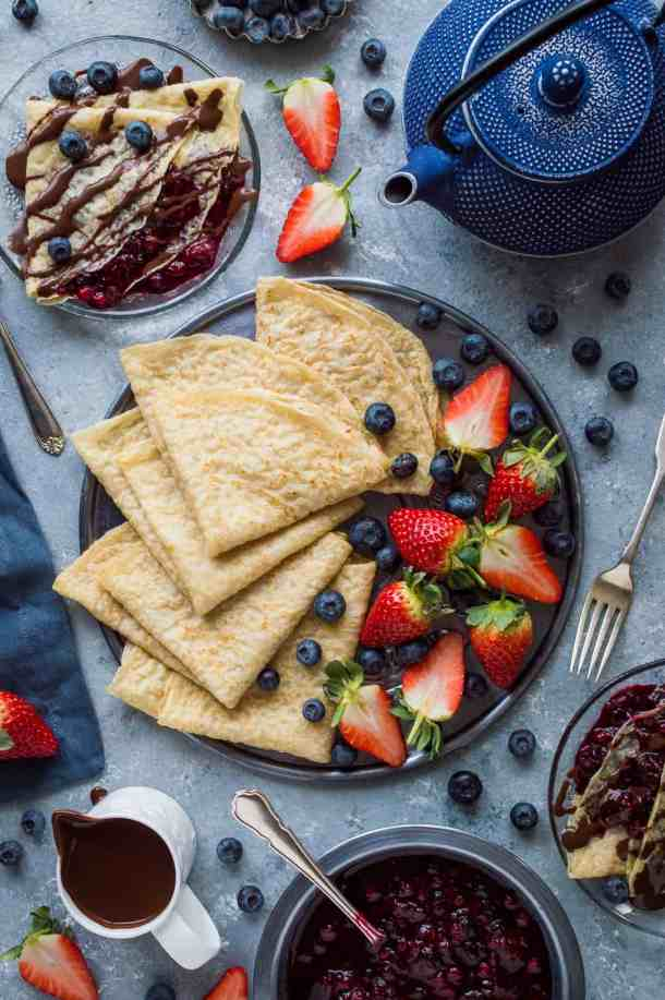 Top down shot of a breakfast spread of vegan pancakes with berries, chocolate sauce and berry compote.