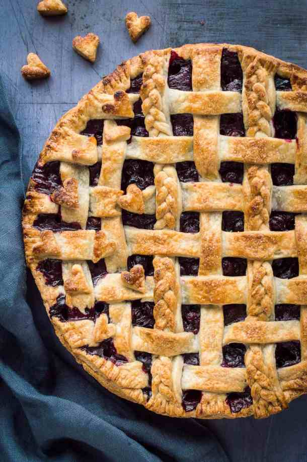 A close up of lattice topped vegan blueberry pie