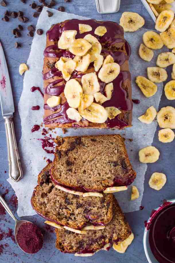 Top down photo of a loaf of vegan chocolate chip banana bread with blueberry glaze and banana chips