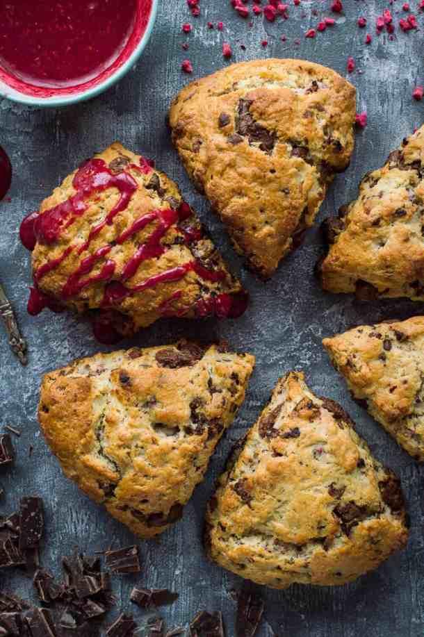 six vegan/dairy free coconut oil chocolate raspberry scones, one drizzled with raspberry glaze.