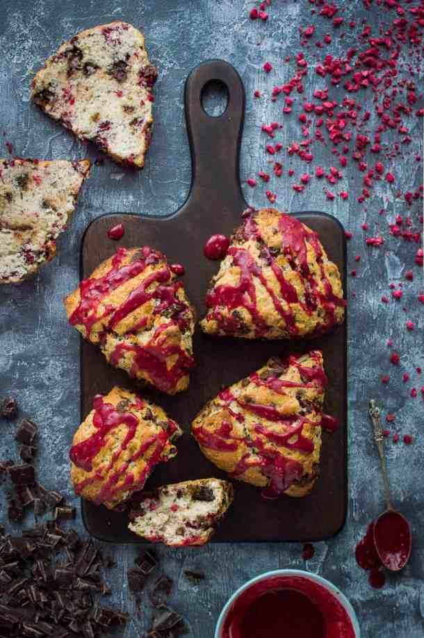 vegan chocolate raspberry scones with raspberry glaze on a wooden board.