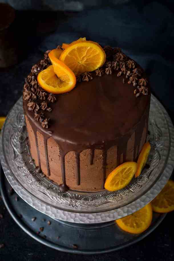 Angled photo of vegan orange and almond cake with chocolate orange vegan buttercream, chocolate drip and candied oranges on a glass plate and silver cake stand.