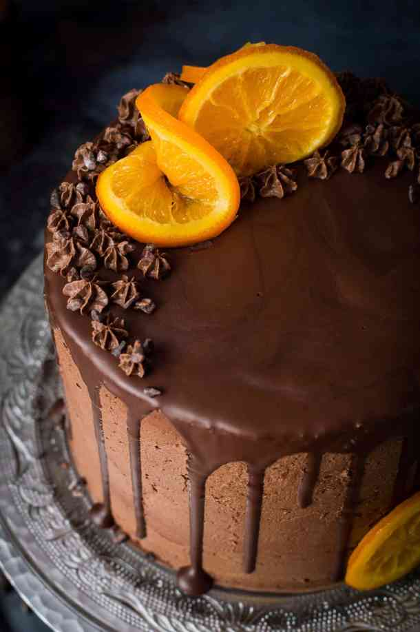 Close up of vegan orange and almond cake with chocolate buttercream, chocolate drip, candied oranges and cacao nibs.