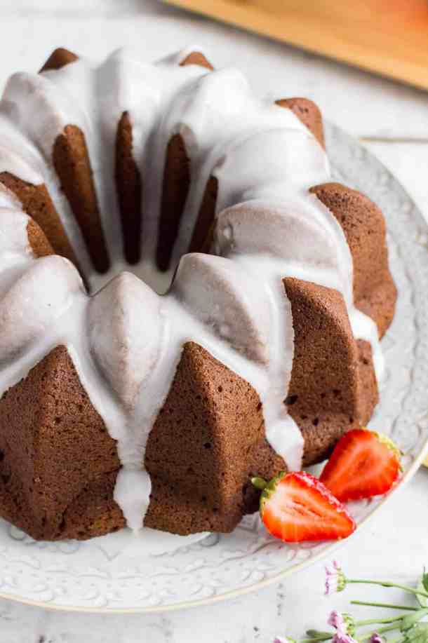 A close up of easy vegan gingerbread bundt cake with lime glaze and strawberries on a white plate and background.