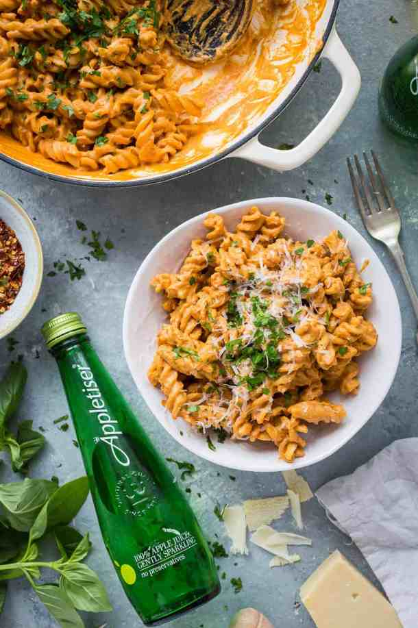 A bowl of vegan creamy roasted red pepper tomato pasta with a bottle of Appletiser.