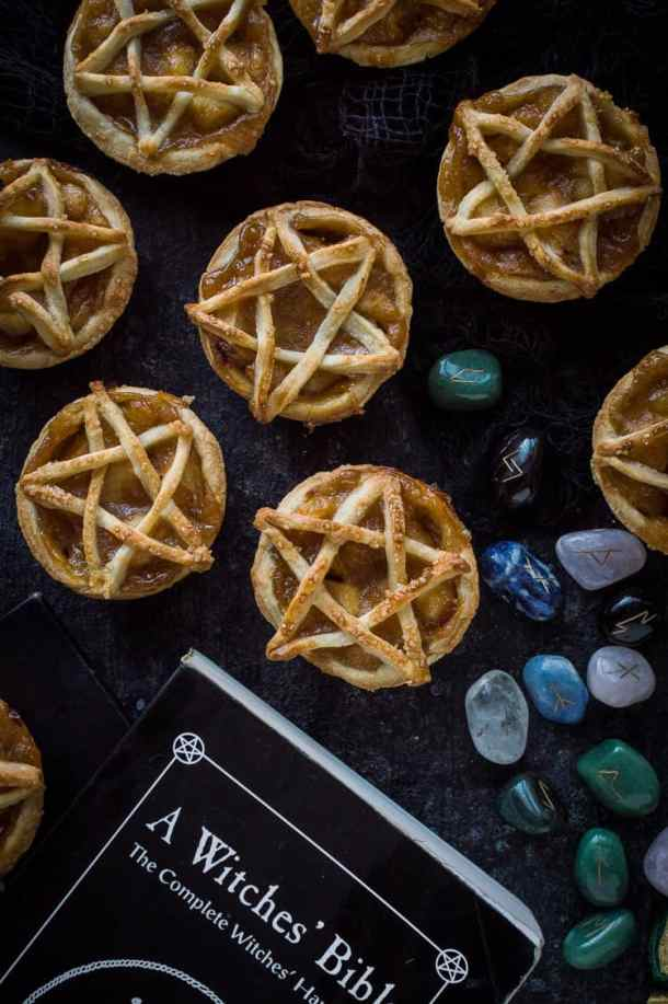 Pentagram topped vegan apple pies for Halloween on a black background with runestones.