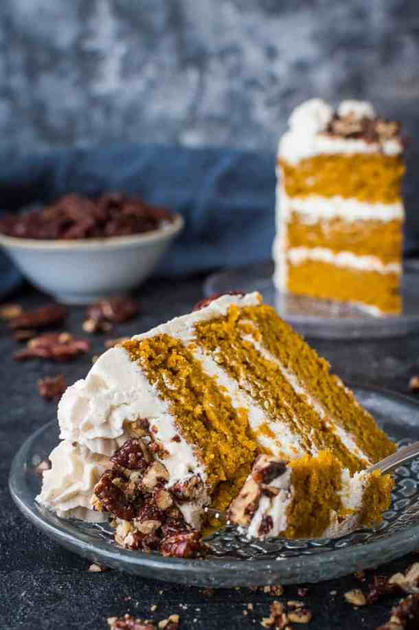 close up of a slice of vegan pumpkin layer cake on a glass plate with a forkful taken out.