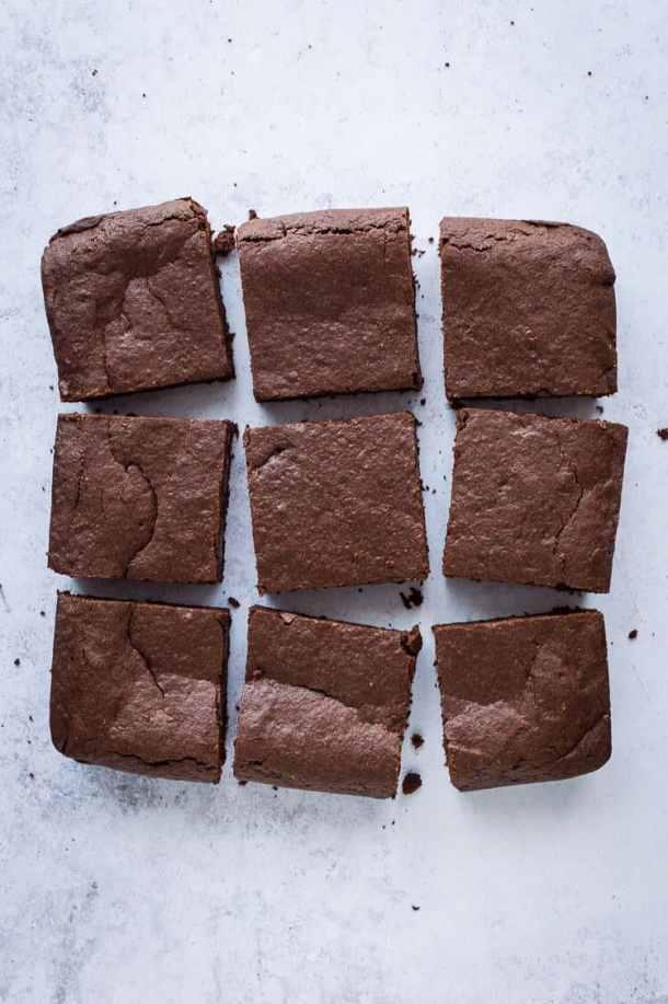Nine vegan mulled wine brownie squares on a grey background.