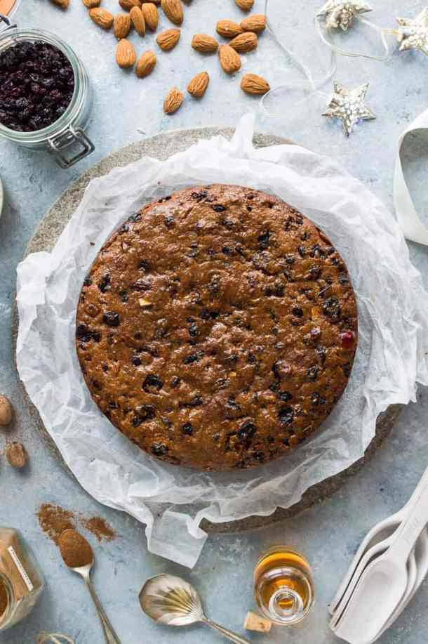 Vegan Christmas fruitcake on white parchment paper surrounded by ingredients.