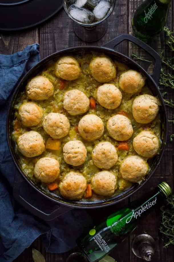 A cast iron pan of vegan vegetable and pearl barley stew with herby dumplings and a bottle of Appletiser on a dark wood background.
