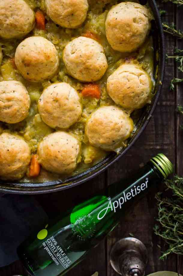 Close up of a pan of vegetable and pearl barley stew with herby dumplings and a bottle of Appletiser