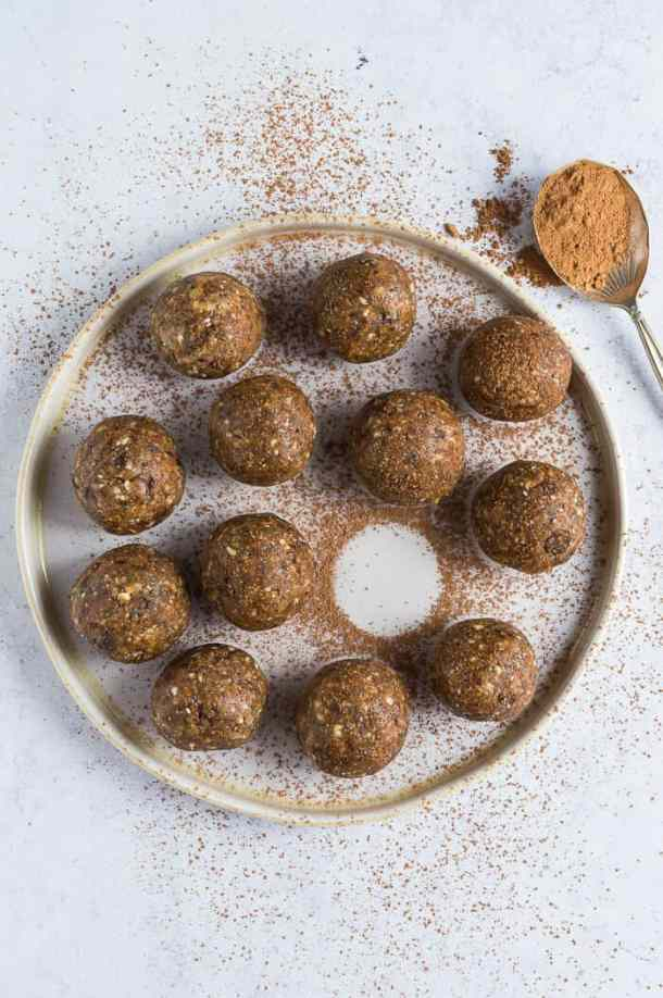 A plate of peanut butter chocolate chip energy bites dusted with cacao powder on a grey background.