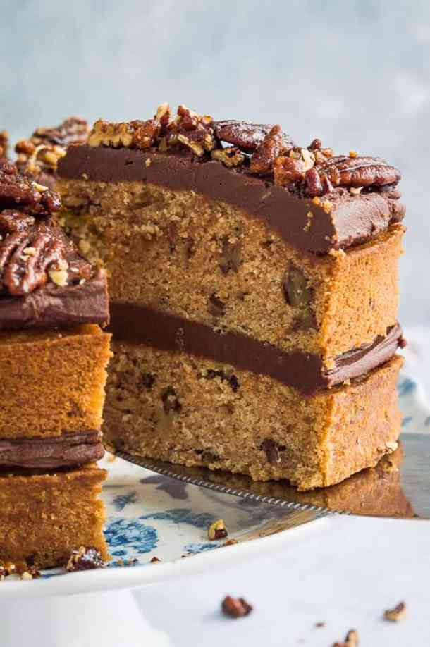 Close up of a slice of vegan, naturally sweetened maple pecan cake with chocolate cashew cream and maple pecans