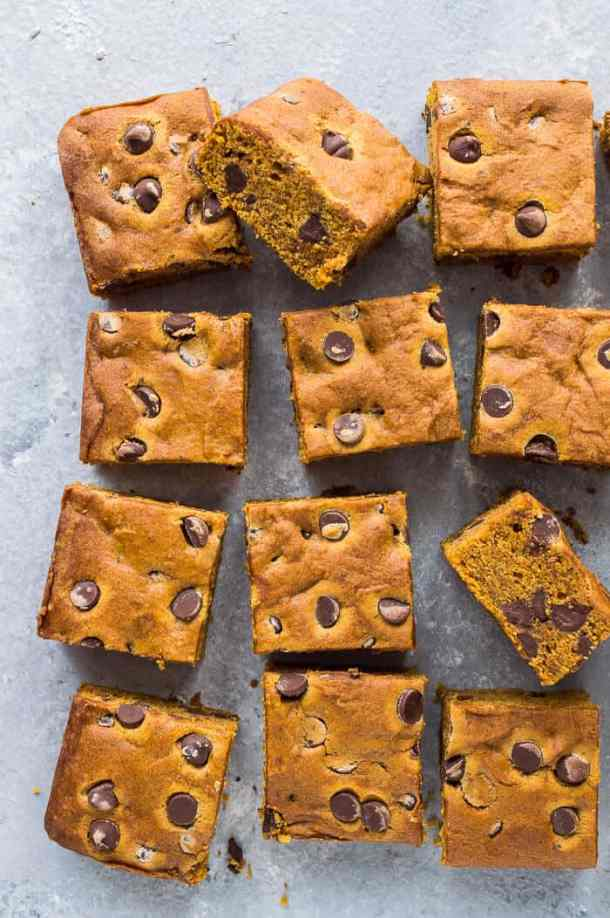 Squares of vegan chocolate chip pumpkin cake on a grey background.
