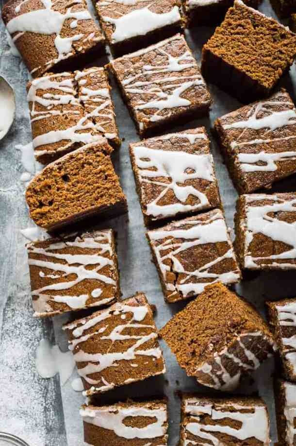 Squares of vegan ginger tray bake cake with lemon glaze on baking parchment on a grey background.