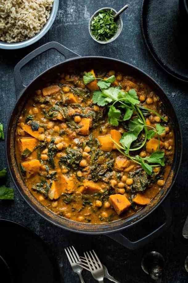 Plant based chickpea, sweet potato and spinach curry in a black cast iron pan on a black background.