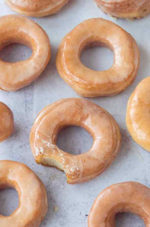 Vegan fried vanilla glazed doughnuts on a grey background, one with a bite taken out.