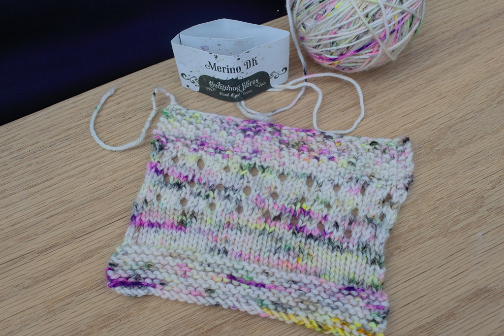 Swatch of garter, stockinette, yarn over and seed stitch in Potluck Colorway of Hedgehog Fibres