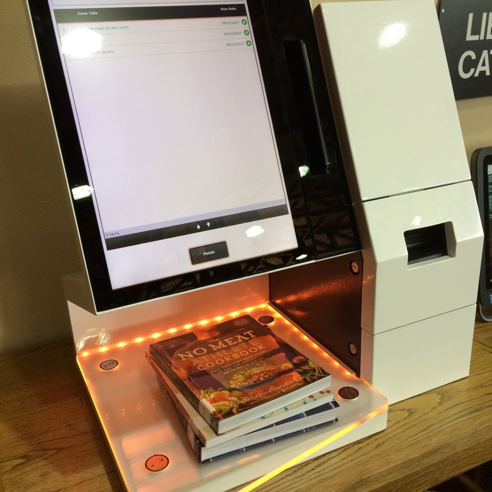 Checking out books with a self-checkout kiosk at library.
