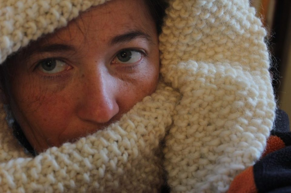Madeleine Roberg of 52 Skeins wrapped up in a fresh hand knit seed stitch scarf