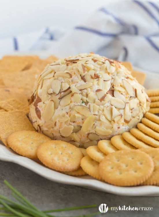 Cheese ball on a plate with crackers.