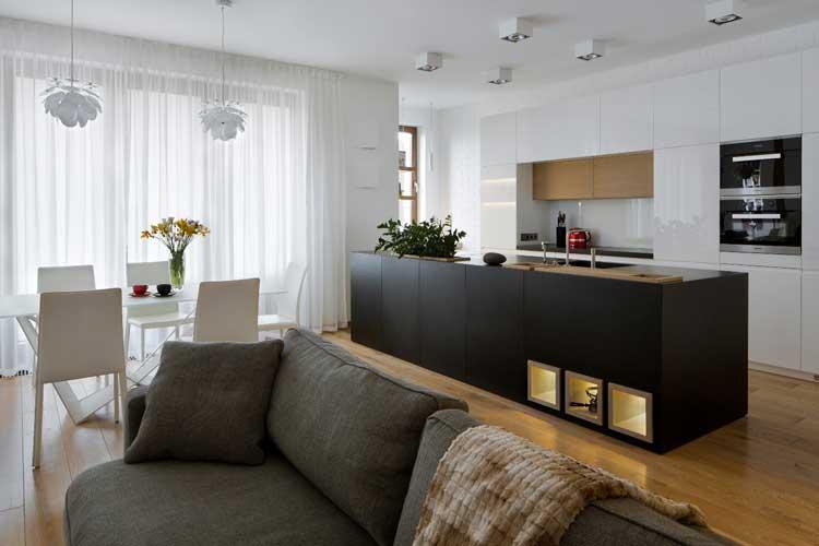 salon z aneksem kuchennym, czarna wyspa, szara sofa, białe meble kuchenne w połysku