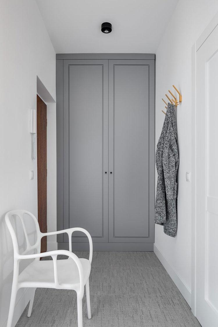 minimalistyczny przedpokój w szarościach z białym krzesłem