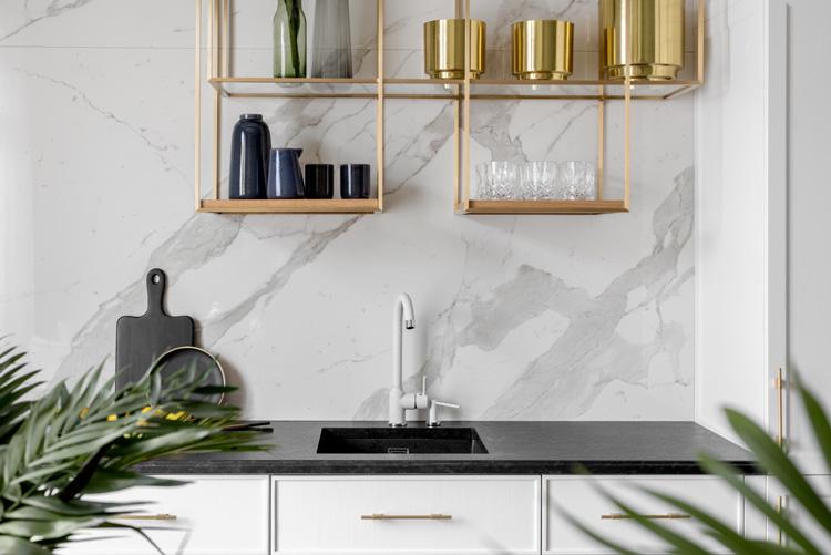 biała kuchnia z czarnym kamiennym blatem i złotymi dodatkami