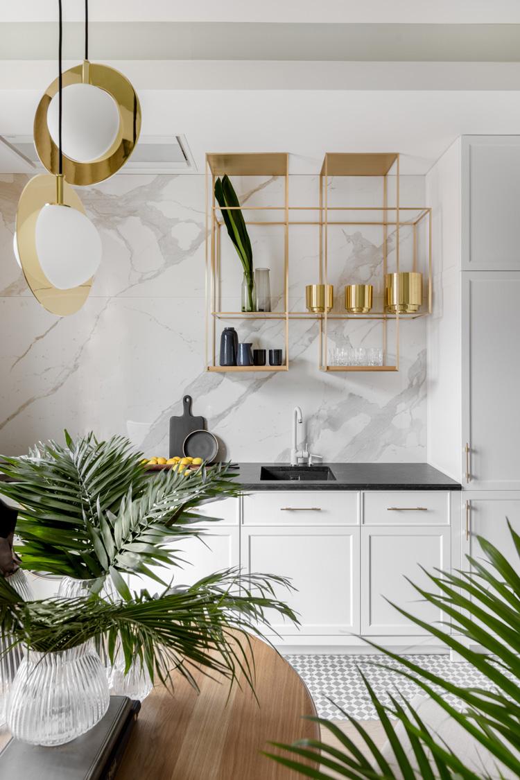 Biała kuchnia, złote dodatki, marmur na ścianie