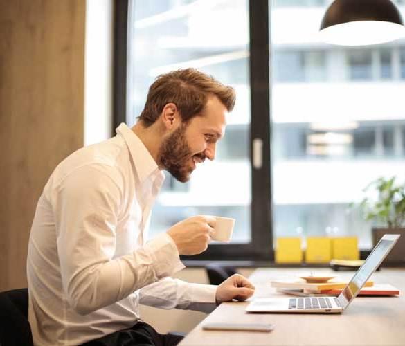 Mężczyzna w biurze pije kawę