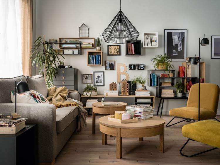 Salon z meblami modułowymi, szarą sofą i dwoma fotelami z żółtą tapicerką.