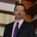 Dr. Claudio Monge wearing a suit and smiling.