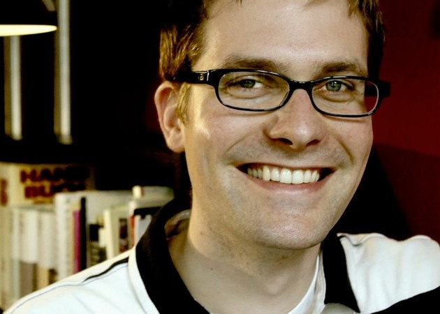 Picture of Dennis Halft smiling and looking into the camera while wearing glasses.