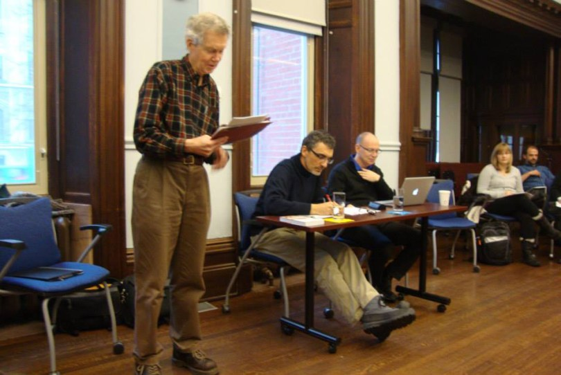 Prof. Michael Vertin standing up and speaking. Claudio Monge and an audience sit in the background.