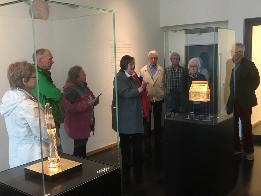Annemarie Lux (M.) vermittelt den ehrenamtlichen Domschatzwächterinnen und -wächtern sowie den Gästeführern der Minden Marketing die Besonderheiten der Ausstellung im neuen Domschatz Minden. Foto: DVM