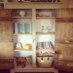 Vintage cupboard with cheeseboards used as shelving