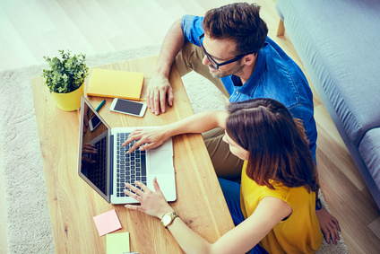 Picture of young couple at home with laptop doing online shopping