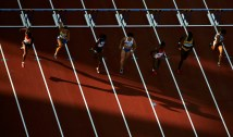 ATHENS - AUGUST 23: Athletes compete in the women's 100 metre hurdle semifinal on August 23, 2004 during the Athens 2004 Summer Olympic Games at the Olympic Stadium in the Sports Complex in Athens, Greece. (Photo by Donald Miralle/Getty Images)