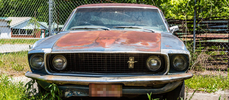 Rusted Ford Mustang and other salvaged cars for sale in a lot