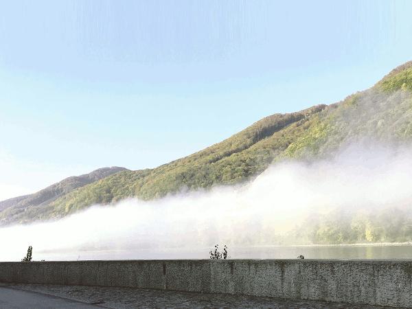 Eine Wolke berührt das Wasser der Donau. Das ist Nebel. Mit zunehmender und wärmender Sonnenstrahlung löst sich dieser bald auf.