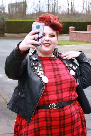 Lindsay is dressed in a tarten red dress, smiling into her phone camera