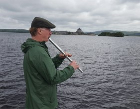 Kevin McGrath, who was part of a group of McGraths from around the world who visited Lough Derg, is pictured playing a tune on the shores of Lough Derg. Photo: Dan McGrath