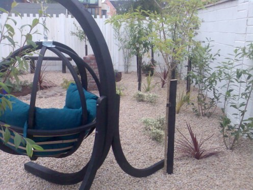 small-garden-low maintenance pebble garden and swing seat