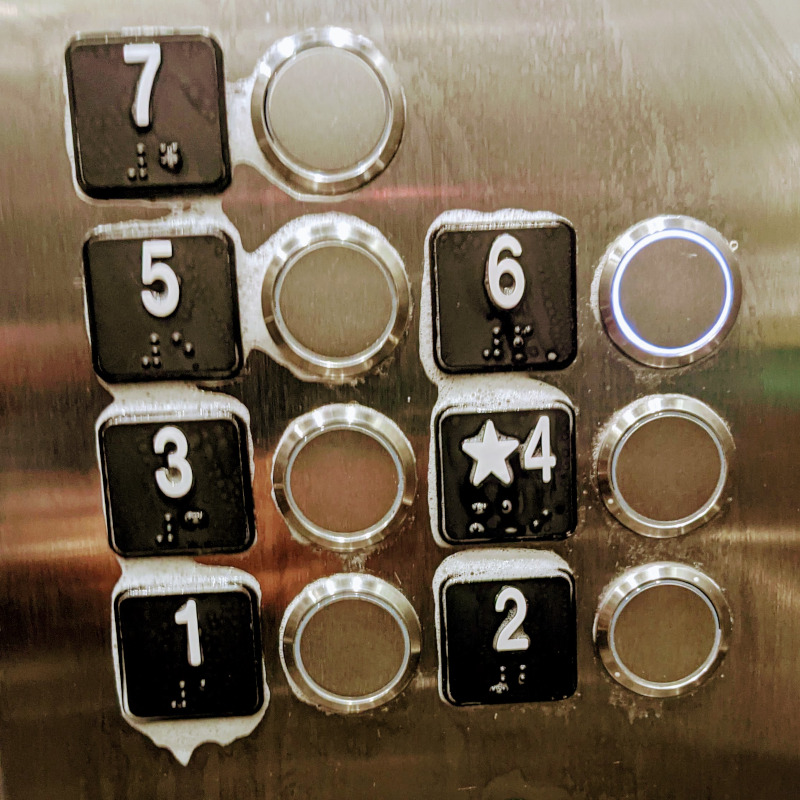 Elevator buttons still damp from being wiped down with disinfectant