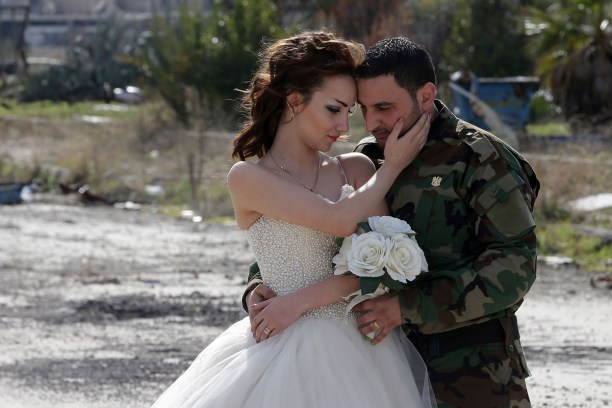 Newly-wed Syrian couple Nada Merhi,18, and Syrian army soldier Hassan Youssef,27, pose for a wedding picture amid heavily damaged buildings in the war ravaged city of Homs on February 5, 2016. A Syrian photographer thought of using the destruction of Homs to take pictures of newly wed couples to show that life is stronger than death. / AFP / JOSEPH EID (Photo credit should read JOSEPH EID/AFP/Getty Images)